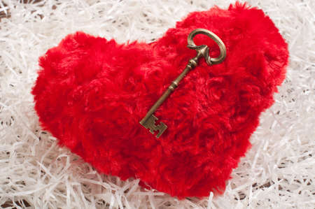 red toy heart on white paper wih the key Stock Photo