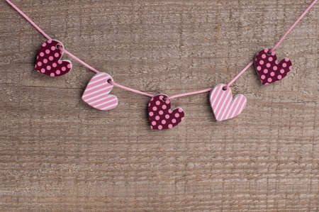 Five hearts on wooden background