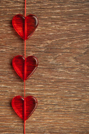 three red hearts on wooden board Stock Photo