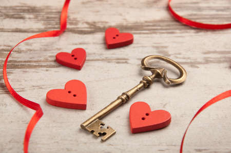 red wooden hearts on wooden board with key and ribbon photo