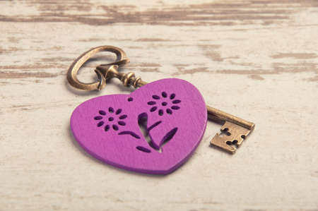 violet wooden heart on wooden desk with key and ribbon photo