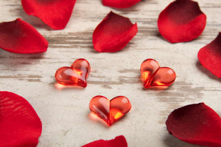 red hearts on the wooden board with petals photo
