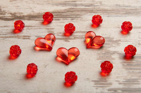 red hearts on wooden board with red plastic roses Stock Photo