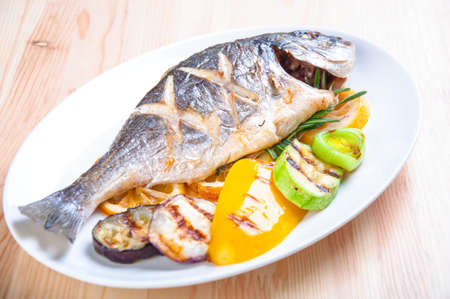 Fried fish with fried vegetables on the plate photo