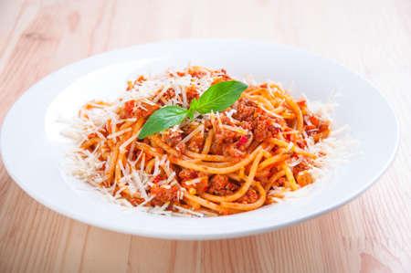 Espaguetis a la boloñesa en plato blanco con salsa de tomate y hojas de albahaca Foto de archivo - 28373308