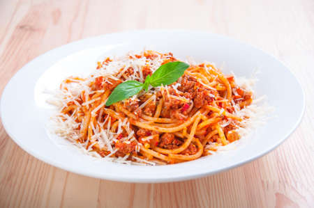 spaghetti bolognese on white plate with tomato sauce and basil leaves Standard-Bild