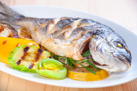 Fried fish with fried vegetables on the plate Stock Photo