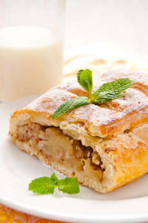 slice of an apple strudel with ta glass of milk
