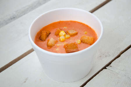 tomato soup with corn and croutons in the plastic box