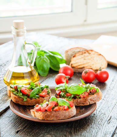 Italian tomato bruschetta with chopped vegetables, herbs and oil on grilled or toasted crusty ciabatta bread