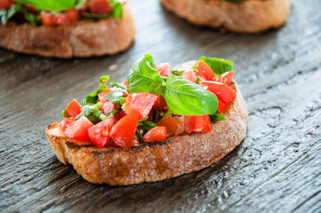 Italian tomato bruschetta with chopped vegetables, herbs and oil on grilled or toasted crusty ciabatta bread Stock Photo