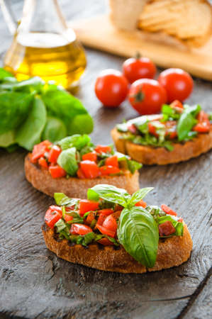 Italian tomato bruschetta with chopped vegetables, herbs and oil on grilled or toasted crusty ciabatta bread Standard-Bild