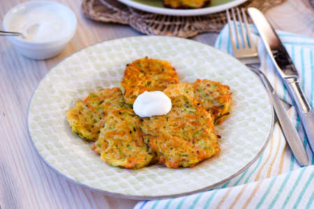 fres: Courgette pancakes served with yogurt on plate