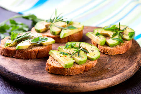 Toast with rye bread and avocado, herbs on wooden board Standard-Bild