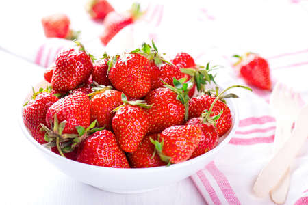 fresh strawberry in white bowl with the red napkin