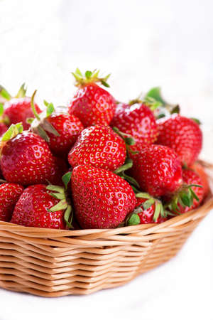 Fresh strawberry harvest in the basket, isolated on white
