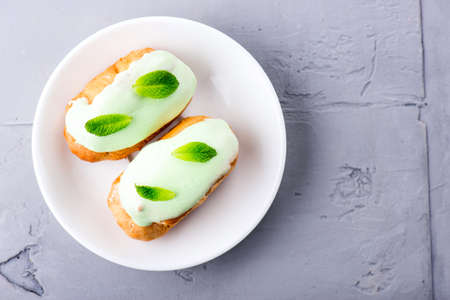 cream dessert eclairs with fresh mint leaves