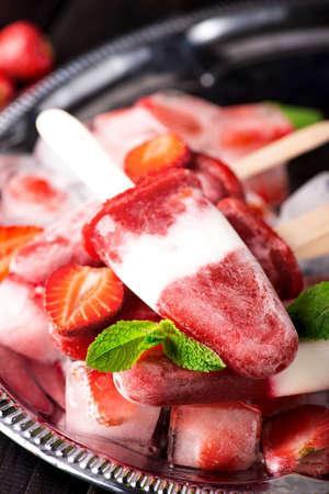 Homemade strawberry yogurt ice cream sicles on dark wooden background Standard-Bild