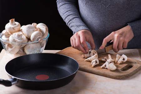 female hands cutting fresh mushrooms on a wooden desk Standard-Bild