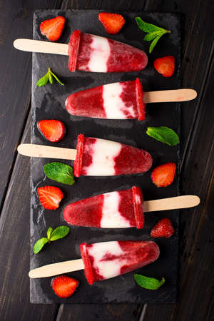 Homemade strawberry yogurt ice cream sicles on slate