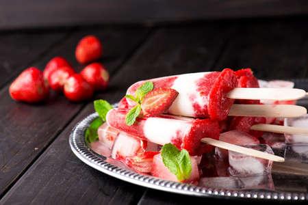 Homemade strawberry yogurt ice cream sicles on dark wooden background Stock Photo