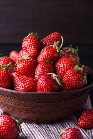 Fresh strawberry in the brown bowl, dark background Standard-Bild