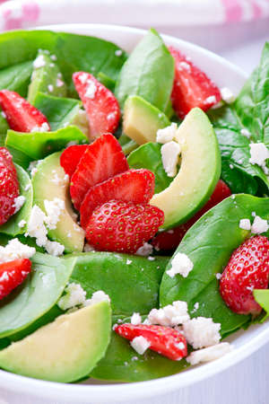 Summer salad with strawberry, avocado and spinach. White table. Standard-Bild