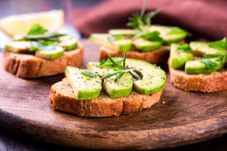 Toast with rye bread and avocado, herbs on wooden board Stock Photo