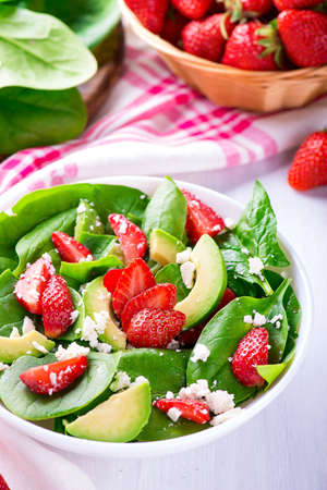 Summer salad with strawberry, avocado and spinach. White table. Stock Photo