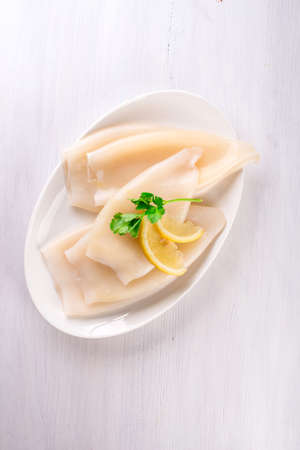Raw squid and ingredients on the white plate