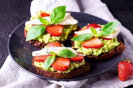 Fresh toast with strawberry on dark plate