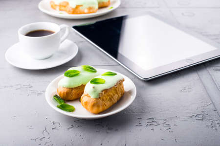 Mint eclairs on a plate, cup of coffee and digital tablet