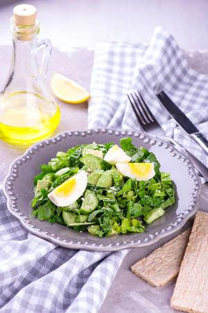 Fresh spinach and avocado salad on grey plate Standard-Bild