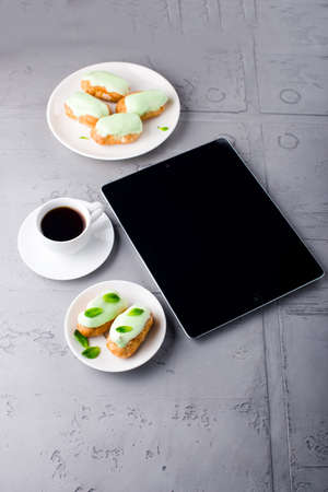 Mint eclairs on a plate, cup of coffee and digital tablet with white screen Standard-Bild
