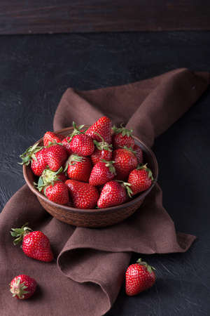 Fresh strawberry in the brown bowl, dark background Stock Photo