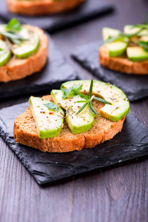 Toast with rye bread and avocado, herbs on slate board