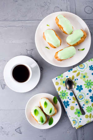Breakfast with mint eclairs and coffee cup. Top view