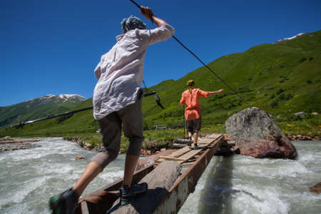 Tourists pass bridge across mountain river