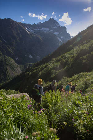 group of tourists descend on the trail among Alpine meadows Stock Photo
