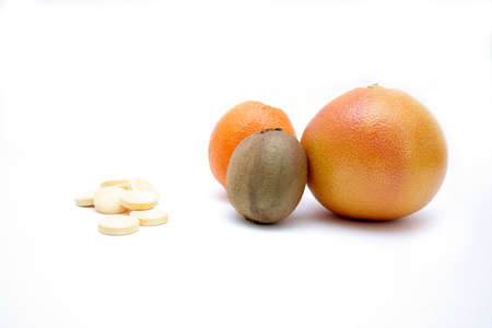 progeny: fresh fruits versus pills, on white surface