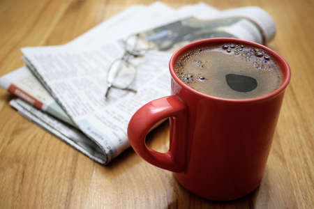 a cup of coffee, a newspaper and a pair of glasses, on a wooden table photo