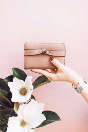 Womens stylish wallet in the hands of a girl with a red manicure on a pink pastel background. A flower in the hand of a girl. The concept of style and fashion. Purse in hand.