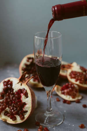 Red wine with an open pomegranate on a textured gray concrete background. A man pours red wine from a bottle into a glass. 写真素材