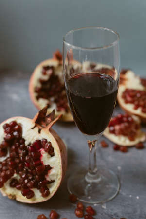 Red wine with an open pomegranate on a textured gray concrete background. Pomegranate seeds on a gray grunge background. The concept of expensive delicious wine 写真素材