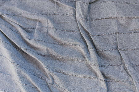 crumpled gray fabric. folds on a gray bedspread. texture of crumpled fabric. blue shadow from the folds.