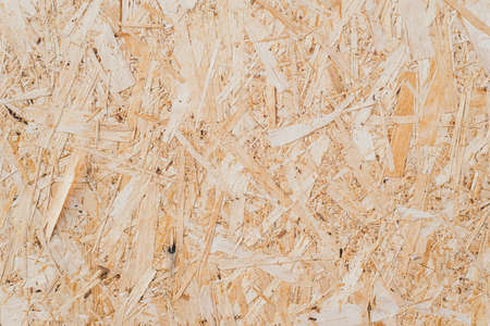pressed sawdust in the board. background of pressed beige wooden sawdust. Imagens - 124784542
