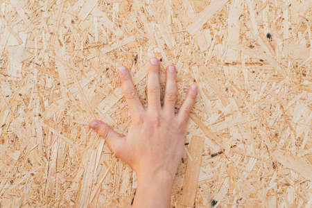 pressed sawdust in the board. Hand on the board of compressed sawdust. background of pressed beige wooden sawdust.