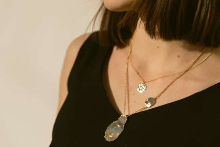 gold pendants around the neck of a girl in the sun. stylish fashion jewelry on the person. jewelry on the brunette. Reklamní fotografie