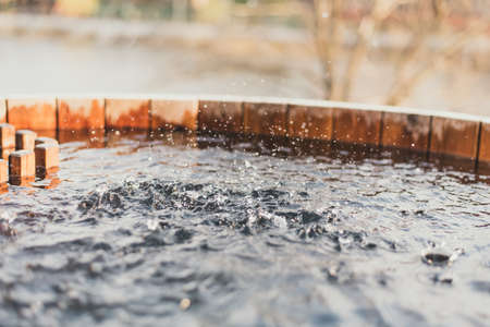 Spray clean water in a well filled. Wooden well with water. Close-up.