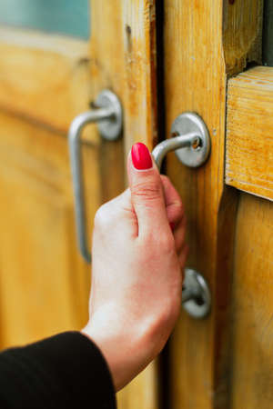 The girl with a thin hand and red manicure opens a wooden old light door with a vertical thin handle. Vertical photo